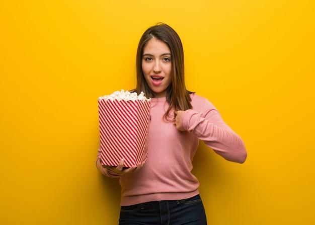 Jeune femme mignonne tenant un seau de pop-corn surprise, réussie et prospère