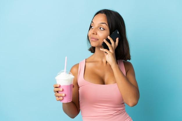 Jeune femme avec milk-shake aux fraises isolé sur fond bleu en gardant une conversation avec le téléphone mobile avec quelqu'un