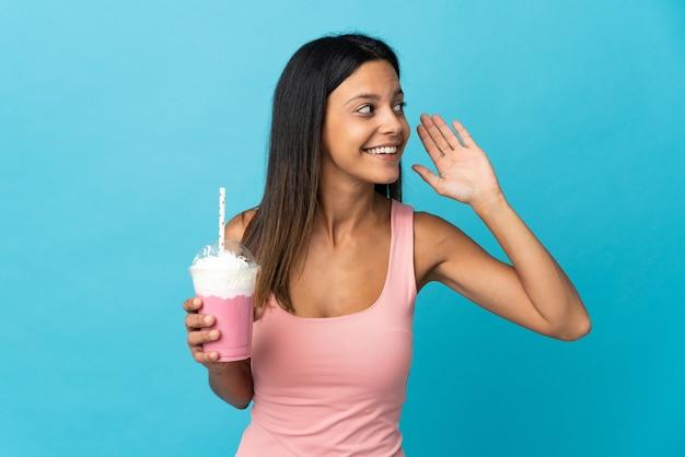 Jeune femme avec milkshake aux fraises en écoutant quelque chose en mettant la main sur l'oreille