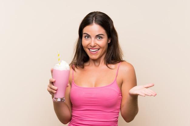Jeune femme avec un milkshake à la fraise avec une expression faciale choquée