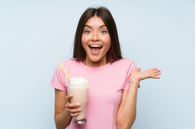 Jeune femme avec un milkshake à la fraise sur un mur bleu isolé avec une expression faciale choquée