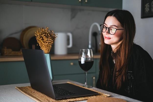 Jeune femme millénaire ayant un appel vidéo sur ordinateur portable et boire du vin, utiliser la technologie pour communiquer avec des amis ou la famille