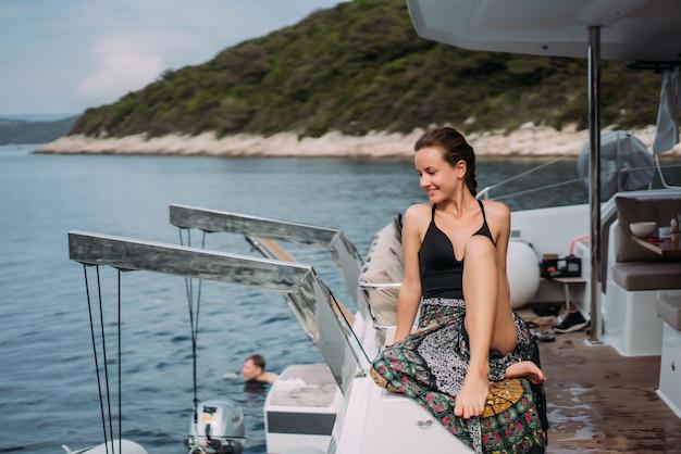 Jeune femme mince assise en bikini maillot de bain sur un yacht et se prélassant au soleil