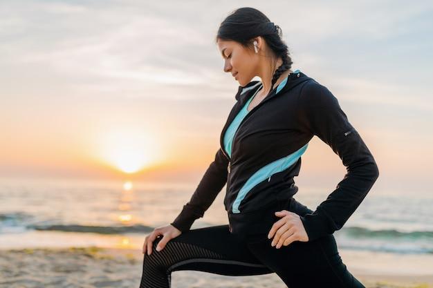 Jeune femme mince attrayante, faire des exercices de sport sur la plage du lever du soleil du matin en vêtements de sport, mode de vie sain, écouter de la musique sur les écouteurs, faire des étirements pour les jambes