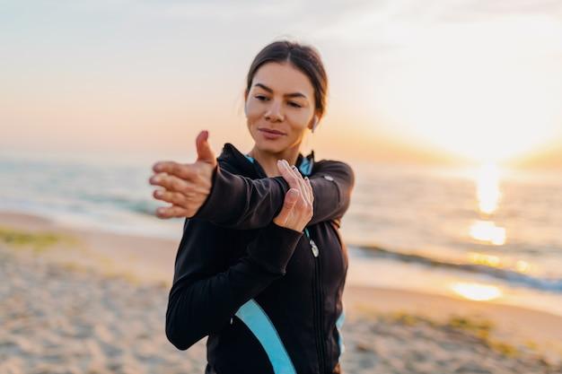 Jeune femme mince attrayante, faire des exercices de sport sur la plage du lever du soleil du matin en vêtements de sport, mode de vie sain, écouter de la musique sur les écouteurs, faire des étirements