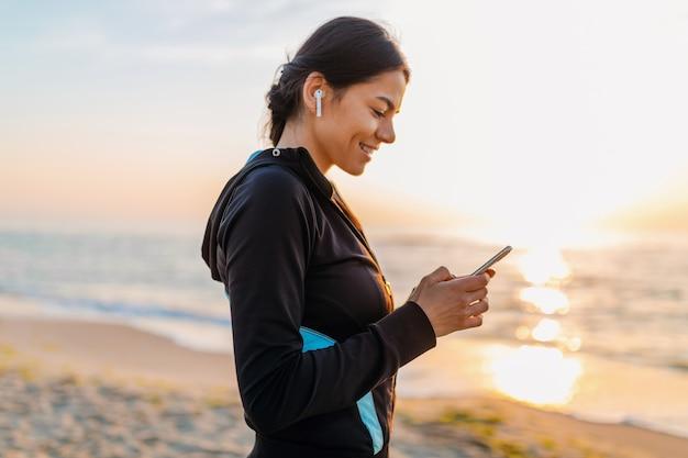 Jeune femme mince attrayante, faire des exercices de sport sur la plage du lever du soleil du matin en vêtements de sport, mode de vie sain, écouter de la musique sur des écouteurs sans fil tenant un smartphone, souriant heureux