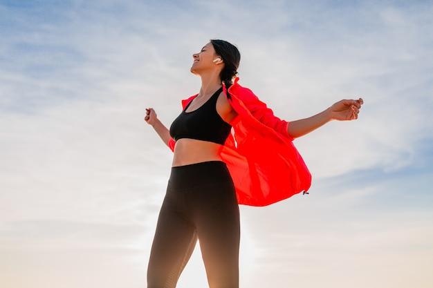 Jeune femme mince attrayante souriante faisant du sport au lever du soleil du matin dansant sur la plage de la mer en vêtements de sport, mode de vie sain, écouter de la musique sur les écouteurs, porter une veste coupe-vent rose, s'amuser