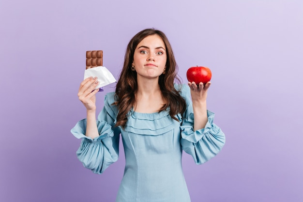 Jeune femme mince choisit entre une pomme saine et un chocolat sucré. brunette ne peut pas décider quoi manger pour le déjeuner.