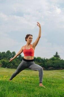 Jeune femme mince étirant ses muscles à l'extérieur appréciant l'harmonie et la paix