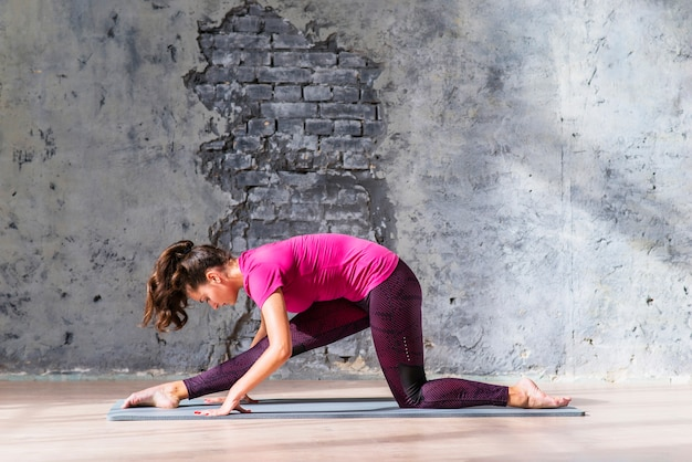 Jeune femme mince de fitness pratiquant le yoga contre un mur endommagé gris
