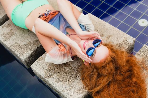 Jeune femme mince gingembre hipster allongé à la piscine, vue d'en haut, cheveux roux colorés, lunettes de soleil bleues, style sport, taches de rousseur, taches de naissance, détendu, heureux, ludique, tenue cool, souriant, sensuel