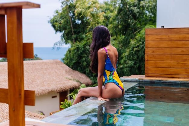 Jeune femme mince heureuse assez positive en maillot de bain coloré au luxe incroyable villa de l'hôtel bénéficiant d'une belle journée en vacances en thaïlande