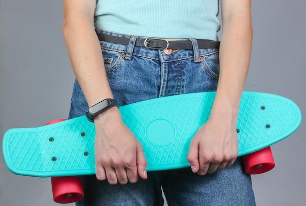 Jeune femme mince en jeans tient une planche à roulettes en plastique dans ses mains sur un fond gris. mode hipster jeunesse.