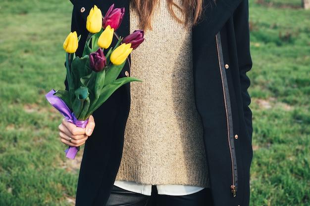 Jeune femme mince en manteau debout sur l'herbe verte et tenant un bouquet de tulipes à la main