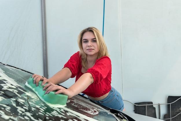 Jeune femme mince nettoyant sa voiture à l'aide d'une mousse haute pression et d'une éponge de lavage de voiture.