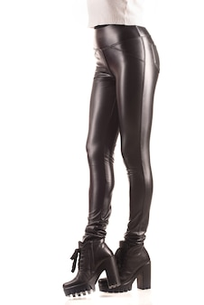 Jeune femme mince non identifiée posant dans des leggings en polyuréthane et des chaussures en cuir à talons sur blanc