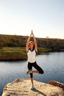 Jeune femme mince pratiquant le yoga en plein air