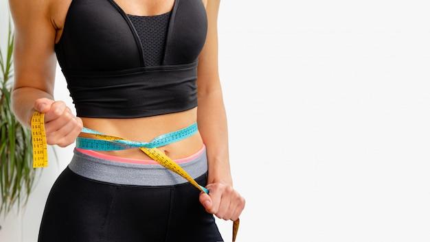Jeune femme mince resserre le ruban à mesurer sur sa taille. concept de mode de vie sportif et de perte de poids. copier l'espace
