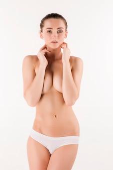 Jeune femme mince, saine et belle en lingerie blanche isolée sur fond blanc
