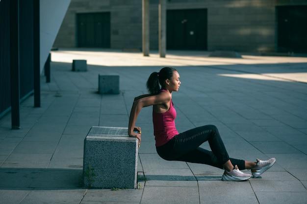 Jeune femme mince et séduisante en vêtements de sport faisant des plongeons inversés sur le cube de pierre