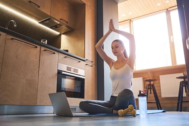 Jeune femme mince sérieuse pratiquant le yoga sur un tapis devant son public en ligne