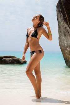 Jeune femme mince sexy, beau corps parfait, peau bronzée, maillot de bain bikini noir, bain de soleil dans l'océan d'eau bleu clair, vacances d'été en asie, sensuel, chaud, voyage en thaïlande, plage tropicale