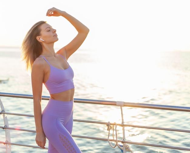 Jeune femme mince sportswear appréciant la musique avec des écouteurs dans ses oreilles. concept d'entraînement du matin au lever du soleil