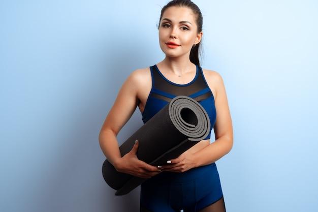 Jeune femme mince, tenant des tapis de yoga dans ses mains