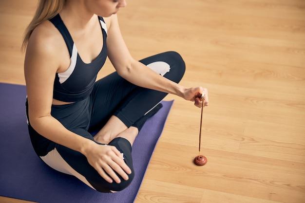 Jeune femme mince en tenue de sport passant du temps seule sur un tapis de yoga en caoutchouc tout en allumant un bâton aromatique