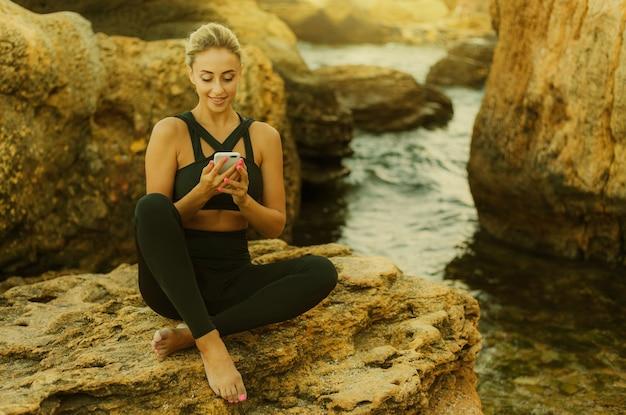 Jeune femme mince en vêtements de sport écoutant de la musique dans des écouteurs et utilisant un smartphone assis sur une pierre sur une plage sauvage