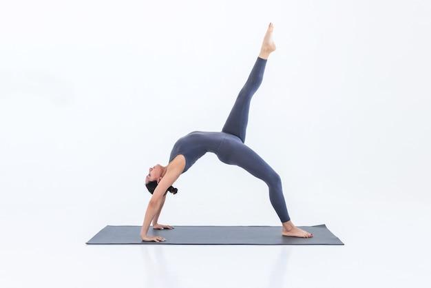 Une jeune femme mince yogi pratique le yoga sur un tapis en faisant une pose de pont. exercice d'étirement