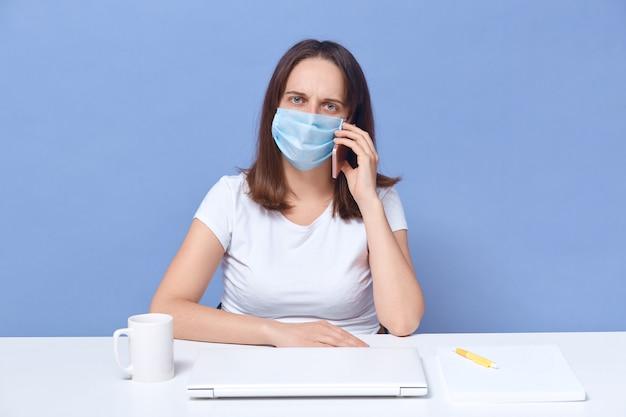 Une jeune femme mise en quarantaine parle au téléphone avec son patron, précise ses tâches pendant l'auto-isolement et le travail à distance