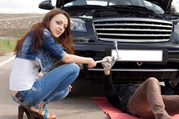 Jeune femme à la mode attirante fixant sa voiture aidant le mécanicien