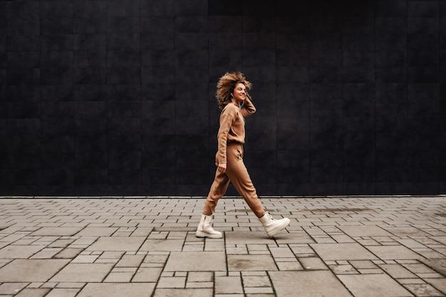 Jeune femme à la mode aux cheveux bouclés marchant dans la rue et écoutant de la musique.