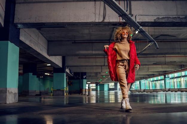Jeune femme à la mode aux cheveux bouclés tenant la main dans la poche de la veste et marchant dans un garage souterrain.