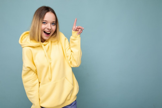 Jeune femme à la mode belle femme en sweat à capuche hipster jaune tendance femme positive montre du visage