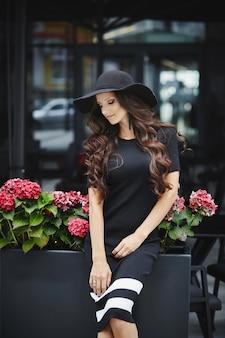 Une jeune femme à la mode dans des lunettes de soleil à la mode et une robe élégante assis à la table du café en plein air