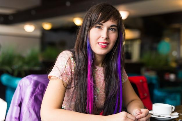 Jeune femme à la mode élégante avec mèche multicolore dans les cheveux se trouve dans le café
