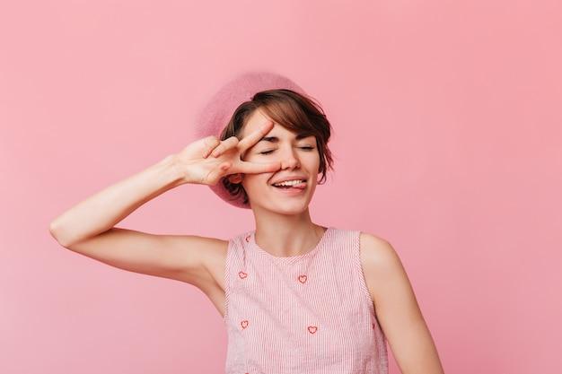 Jeune femme à la mode montrant le signe de la paix