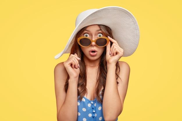 Jeune femme à la mode portant un chapeau posant contre le mur jaune