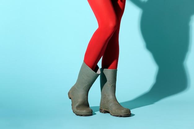 Jeune femme à la mode portant un collant rouge, des collants ou des bas de corps et des bottes en caoutchouc