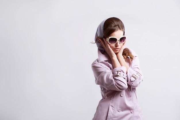 Jeune femme de mode qui pose en studio avec manteau rose et lunettes de soleil blanches.