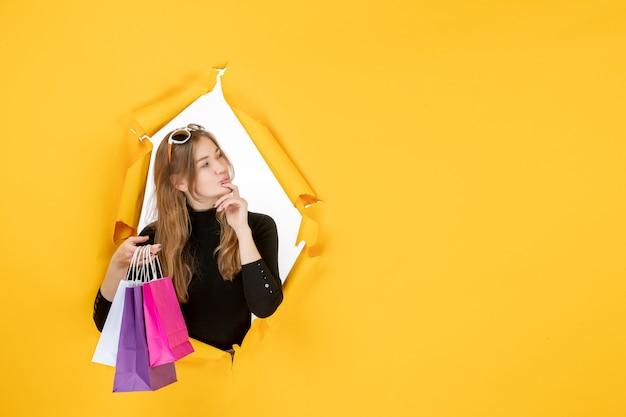 Jeune femme de mode avec des sacs à provisions à travers un trou de papier déchiré dans le mur