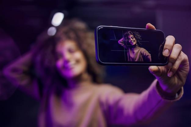 Jeune femme à la mode souriante aux cheveux bouclés prenant selfie.