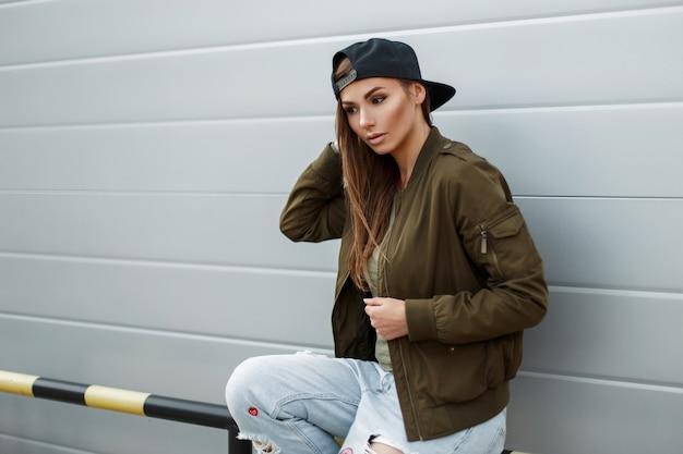 Jeune femme à la mode avec des taches de rousseur dans des vêtements de rue élégants avec une casquette de baseball