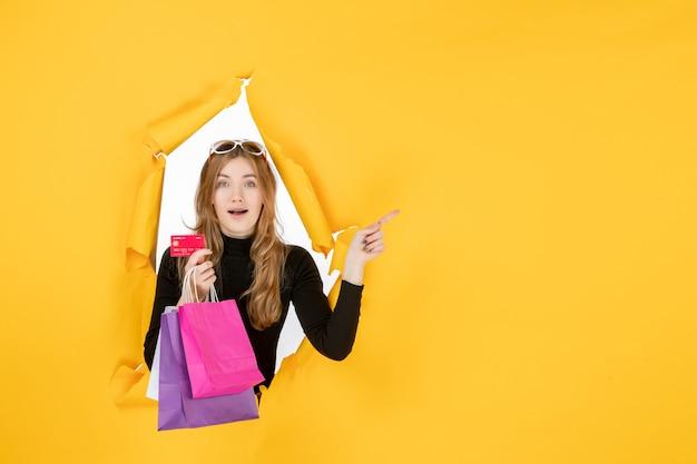 Jeune femme de mode tenant des sacs à provisions et une carte de crédit à travers un trou de papier déchiré dans le mur