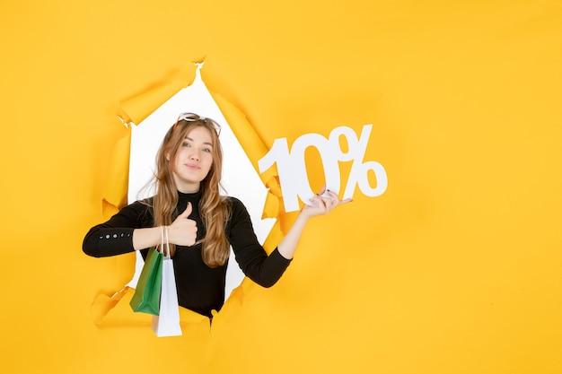 Jeune femme de mode tenant des sacs à provisions et pourcentage de remise à travers un trou de papier déchiré dans le mur