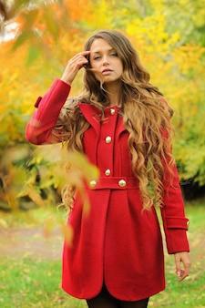 Jeune femme de mode vêtue d'un manteau rouge dans le parc en automne.