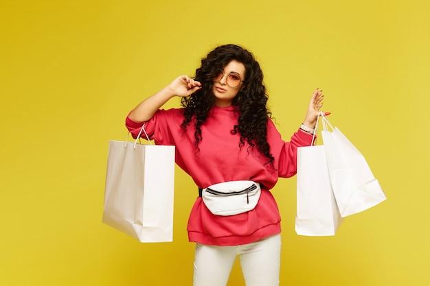 Jeune femme modèle dans un sweat à capuche rose et lunettes de soleil modish posant avec des sacs à provisions sur fond jaune, isolé avec copie espace