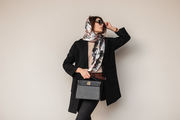 Jeune femme modèle élégant féminin dans des lunettes de soleil à la mode dans des vêtements noirs à la mode luxueux avec un sac à main en cuir avec une écharpe élégante sur la tête près du mur dans la rue. belle fille. dame d'affaires